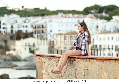 Happy Teenage Girl Sitting On A Ledge Contemplating Landscape In A Town Outskirts