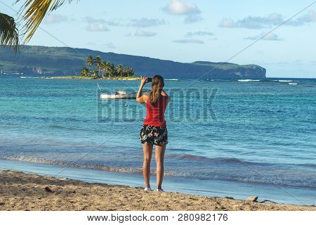Traveler Girl Taking Photo On Tropical Beach. Young Girl Traveler Relaxing In Vacation. Traveler Tak