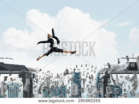 Business Woman Jumping Over Gap With Flying Letters In Concrete Bridge As Symbol Of Overcoming Chall