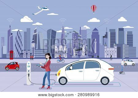 Woman Charging An Electric Car In A London Street With People Walking And The City Skyline At The Ba