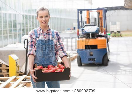 Portrait of smiling farmer with tomatoes in crate against forklift