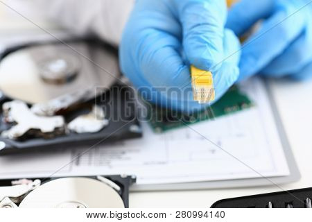 A Male Hand In Blue Protective Gloves Holds A Network Connector. The Lan Constructor Deconstructs Th
