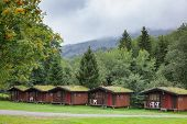 Wooden cabins with sod or turf roof at a campsite in Norway Scandinavia poster