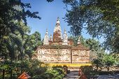 Beautiful and ancient Maha chedi of Wat Chet Yot, surrounded by trees and vegetation in Chiang Mai, Thailand. poster