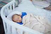 Adorable baby girl sleeping in the crib. Little child having a day nap in cot. Infant kid resting in nursery poster