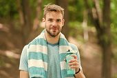 Drink some water. Man jogger with towel on shoulders holds water bottle. Man athlete sport clothes refreshing. Sport and healthy lifestyle concept. Athlete drink water after training in park. poster