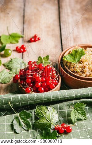 White Currant And Red Currant With Leaves In Wooden Bowls On A Wooden Background. Close Up, Copy Spa