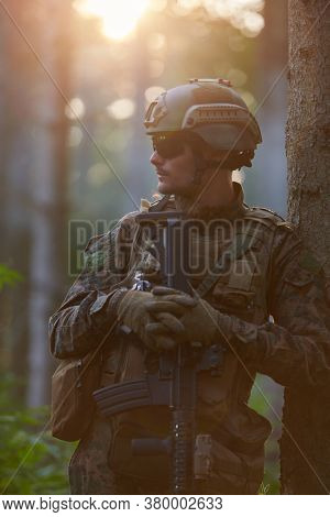 soldier portrait with  protective army tactical gear  and weapon having a break and relaxing