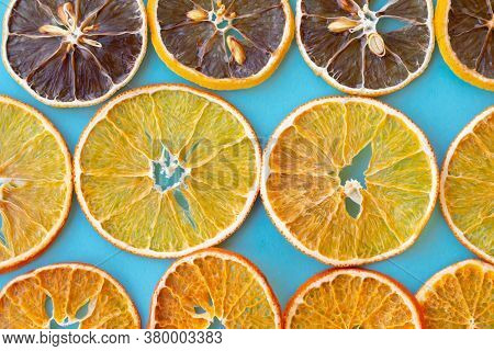 Pattern Of Dehydrated Citrus Fruits As Lemons, Tangerines, Oranges On Blue Background. Slices Of Dri