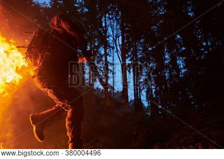 Soldier in Action at Night in the Forest Area. Night Time Military Mission jumping over fire