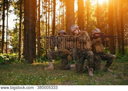 Soldier fighters standing together with guns. Group portrait of US army elite members, private military company servicemen, anti terrorist squad