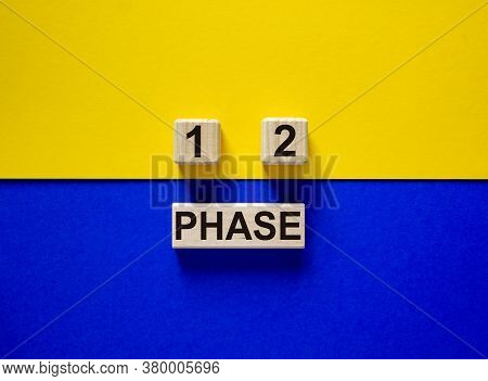 Wooden Block With Word 'phase'. Wooden Cubes With Numbers 1 And 2. Beautiful Yellow And Blue Backgro