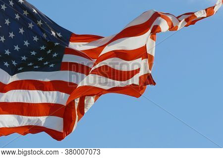 Big American Flag Unfolds In The Wind Against A Blue Sky, Copy Space. Huge American Flag Appears In