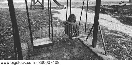 Little Girl On The Swing. The Girl Is Sad Alone On The Playground. Monochrome Black And White Image.