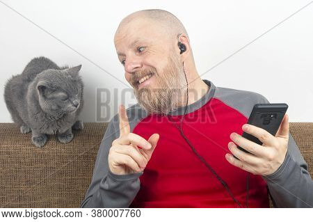 Bearded Man Listens With Pleasure At Home To His Favorite Music From The Phone With Small Headphones