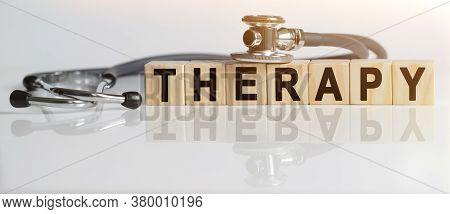 Therapy The Word On Wooden Cubes, Cubes Stand On A Reflective White Surface, On Cubes - A Stethoscop