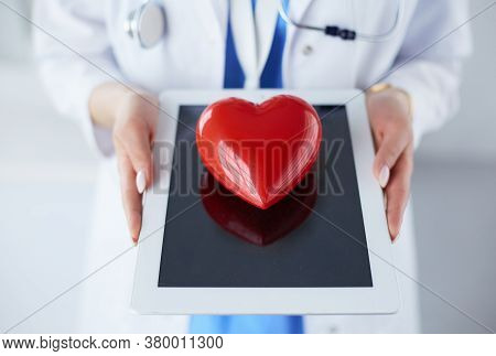 Female Doctor With Stethoscope Holding Heart, On Light Background