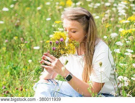 A Woman Holding A Posy And Sniffing Flowers On A Meadow In The Afternoon