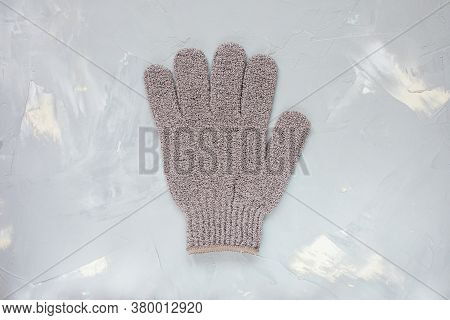 Exfoliating Massage Glove For Shower On Gray Background. Bath, Spa And Cellulite Treatment Concept