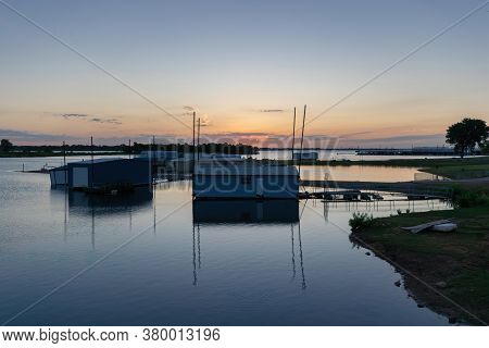 Boathouses In A Marina On A Calm Lake Shoreline As The Sun Rises On The Horizon Behind A Few Low Clo