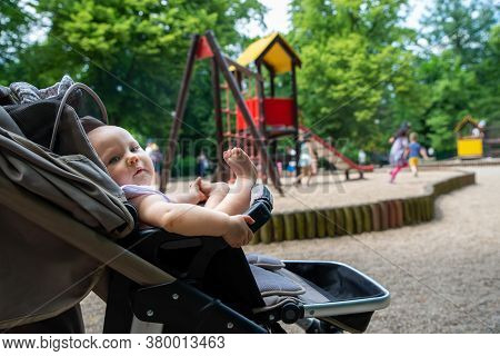 A Small Child On The Playground In A Pram