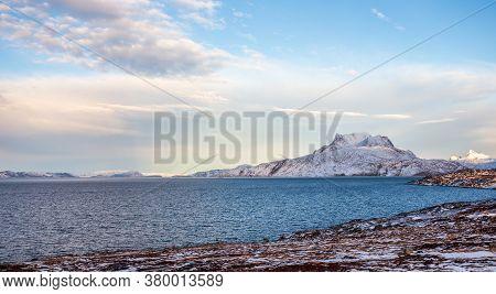 Frozen Tundra Landscape With Cold Greenlandic Sea And Snow Sermitsiaq Mountain In The Background, Ne