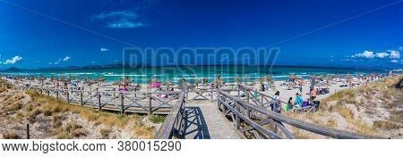 PLAYA DE MURO, Mallorca, Spain - 23 July 2020 - People enjoying hot summer day on popular sandy city beach in Mallorca.