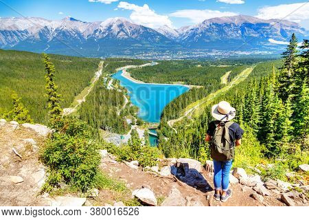 Hiker Standing On Top Of Grassi Lakes Trail Overlooking The Town Of Canmore In Kananaskis With Sceni