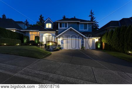 Modern Suburban Home Exterior On A Late Summer Evening With Lights On Yard And House
