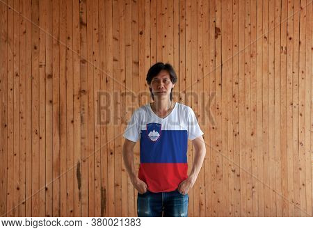 Man Wearing Slovenia Flag Color Shirt And Standing With Two Hands In Pant Pockets On The Wooden Wall