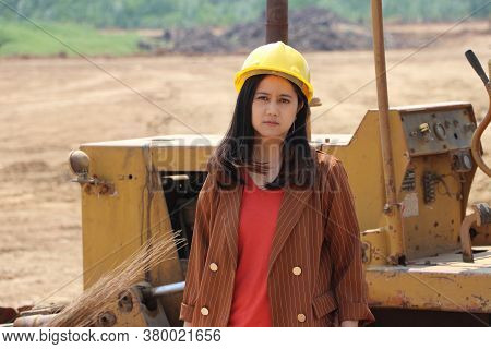 Female Civil Engineer Or Architect With Yellow Helmet Standing With Bulldozer Truck With Front Loade