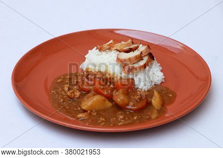 Yellow Curry Chicken Or Japanese Curry With Cooked Rice In The Round Orange Color Of Dish On The Whi