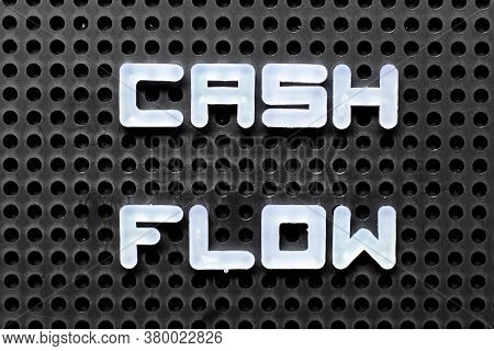 White Color Alphabet With Word Cash Flow On Black Pegboard Background