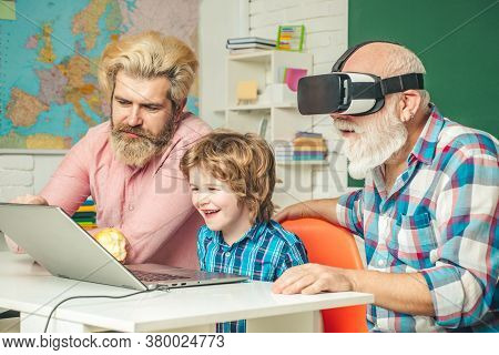 Three Generations Of Men Having Fun Together. Grandfather, Father And Son Playing Computer Games At