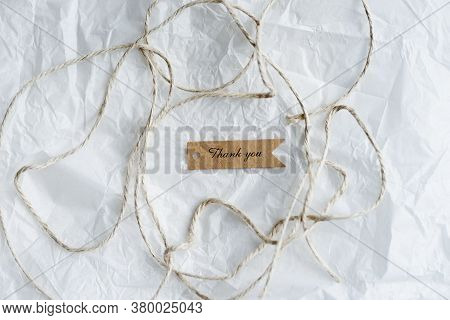 Thank You Craft Brown Tag And Recycle Craft Wire On White Crumpled Paper With Copy Space , Idea For