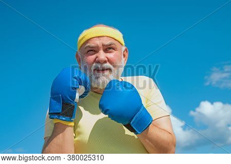 Senior Sportive Man In Boxing Stance Doing Exercises With Boxing Gloves. Healthy Fighter Senior Old
