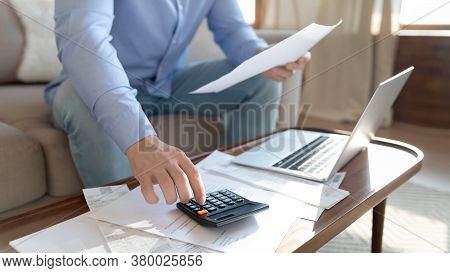 Young Man Calculating Monthly Household Expenditures Alone At Home.