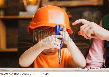 Child With A Screw-driver. Kid Boy Using A Screw Driver. Early Childhood Education Concept