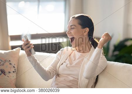 Overjoyed Young Girl Looking At Mobile Screen, Making Yes Gesture.