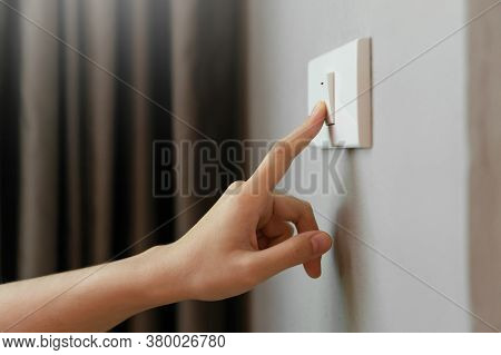 Close Up Of Female Finger Is Turn Off On Lighting Switch At Home. Power, Energy, Saving Electrical,