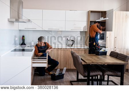 Full Length Shot Of Two Handymen, Workers In Uniform Assembling Kitchen Cupboard, Cabinet Using Scre