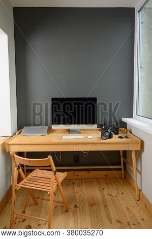 Photographer's Workplace With Professional Camera And Computer
