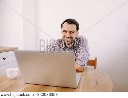 Happy Smiling Man In Shirt With A Cup Of Coffee Works On Laptop