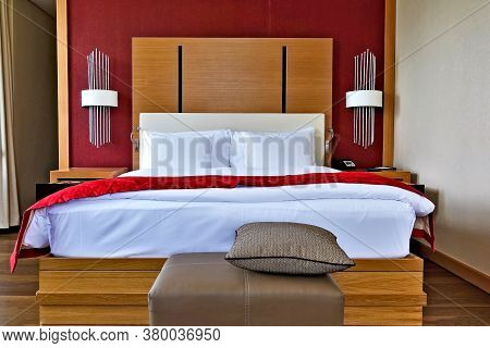 The Interior Of The Hotel. Double Bed With White Linen And Red Bedspread. Wooden Panel At The Head,