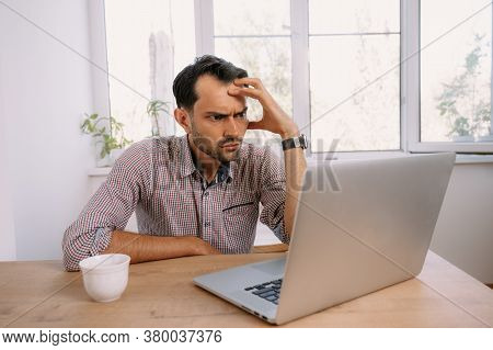 Angry Man In Shirt With A Cup Of Coffee Works On Laptop