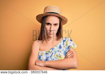 Young beautiful woman wearing casual t-shirt and summer hat over isolated yellow background skeptic and nervous, disapproving expression on face with crossed arms. Negative person.