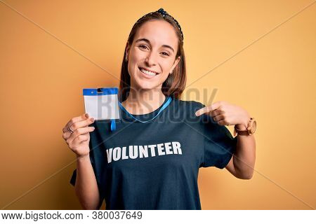 Young beautiful woman wearing volunteer t-shirt doing volunteering holding id pass card with surprise face pointing finger to himself