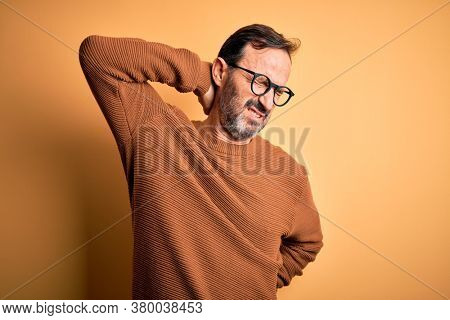 Middle age hoary man wearing brown sweater and glasses over isolated yellow background Suffering of neck ache injury, touching neck with hand, muscular pain