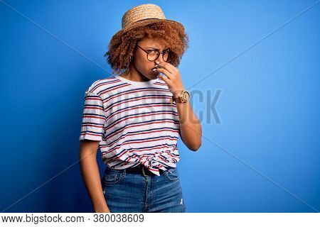 African American woman with curly hair on vacation wearing summer hat and striped t-shirt smelling something stinky and disgusting, intolerable smell, holding breath with fingers on nose. Bad smell