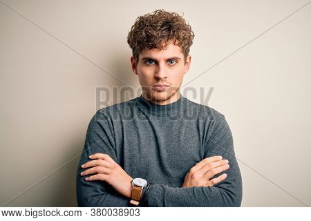 Young blond handsome man with curly hair wearing casual sweater over white background skeptic and nervous, disapproving expression on face with crossed arms. Negative person.